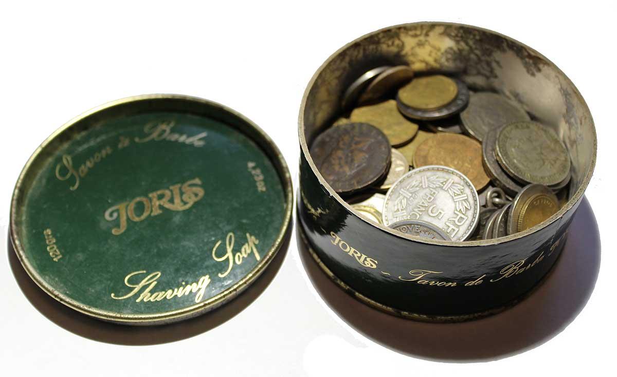 Une boite de savon à barbe rempli de vielles pièce de monnaie en vrac...