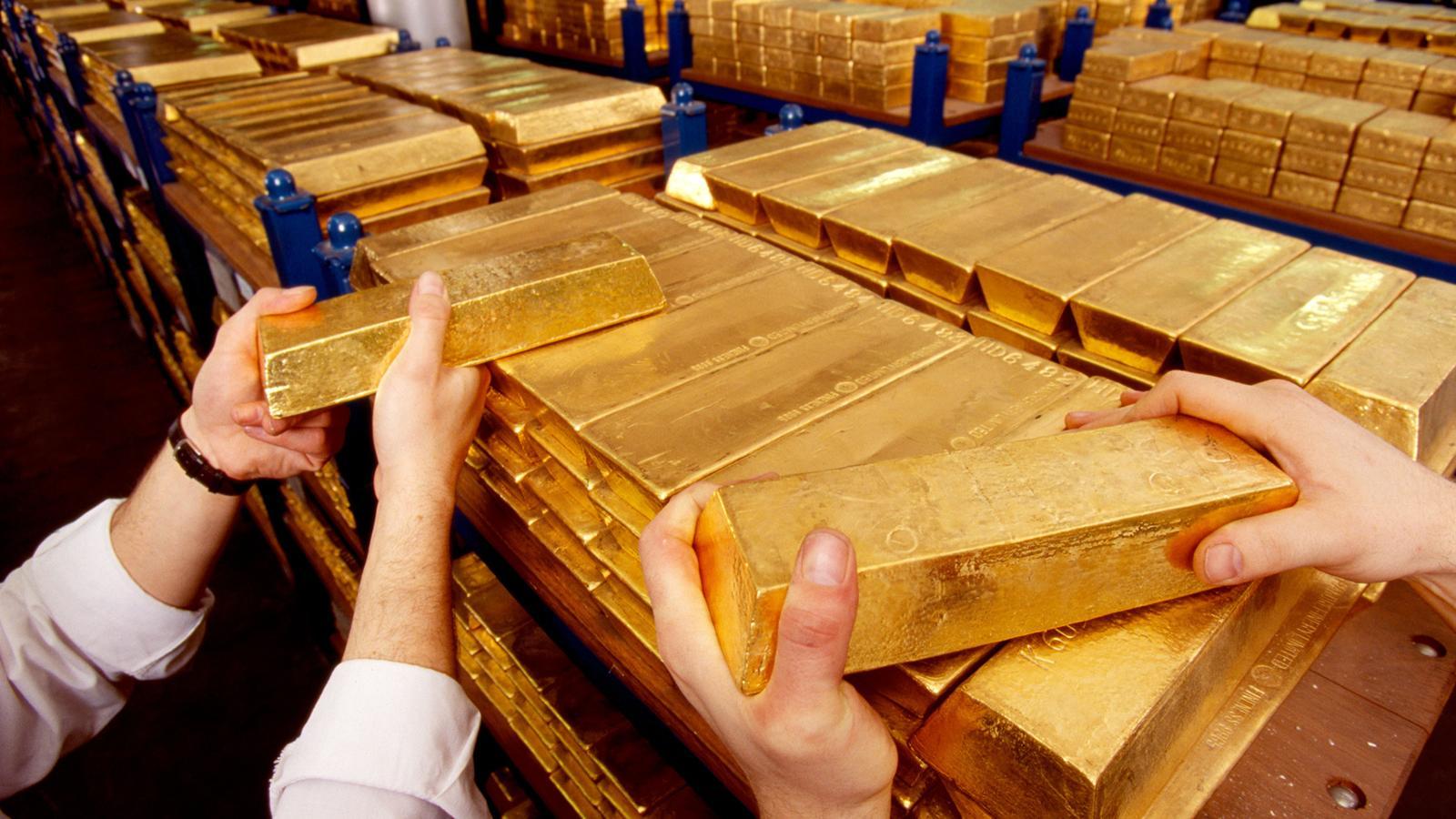 Les barres d'or de 12 kilos sont alignées sur des étagères bleues